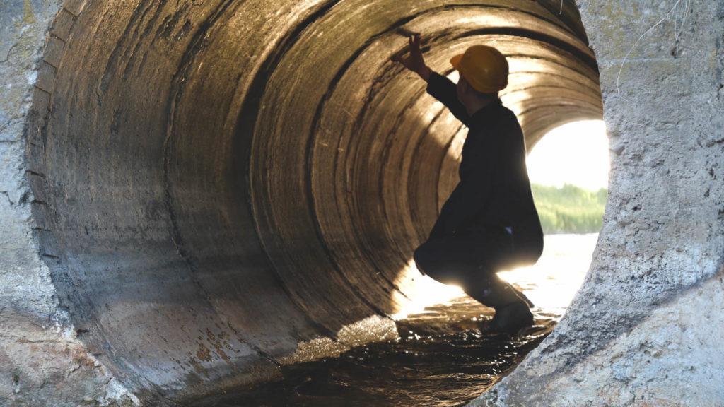 Ansicht eines Bauingeneurs, der einen Abwasserkanal überprüft